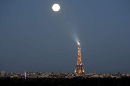 A super moon rises in the sky near the Eiffel tower as seen from Suresnes, Western Paris, France, September 27, 2015. The astronomical event occurs when the moon is closest to the Earth in its orbit, making it appear much larger and brighter than usual. REUTERS/Charles Platiau